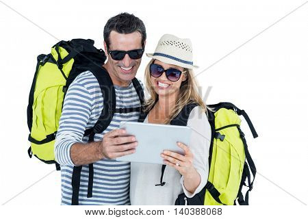 Cheerful couple with luggage looking in digital tablet against white background
