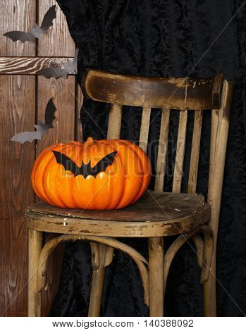 decorations for Halloween holiday - an old chair, origami bats and pumpkin