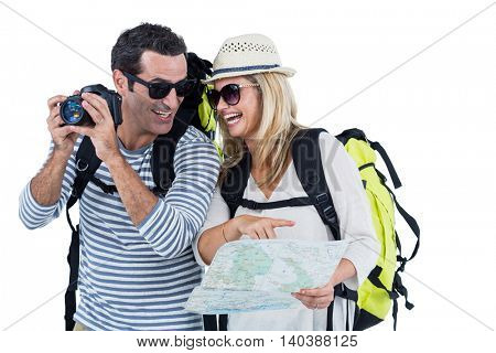 Cheerful couple with camera and map carrying luggage against white background