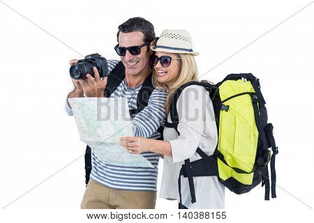 Cheerful couple looking in camera while carrying luggage against white backgroud