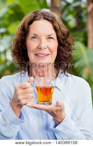 Portrait of smilng mature woman drinking herbal tea