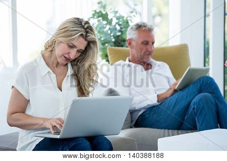 Mature couple using technology while sitting at home