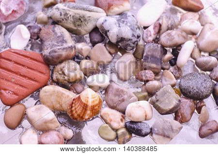 Colorful pebbles on the beach. Background with color stones on the sea. Sea shore bright stones pebble gravel boulder.