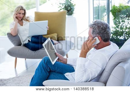Man talking on phone while holding tablet with woman at home