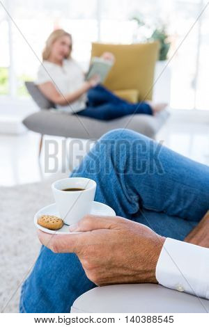 Midsection of man having breakfast at home with woman in background