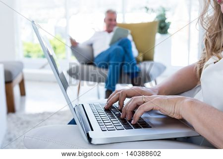 Midsection of woman with laptop by man using technology at home