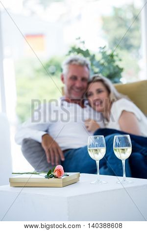White wine by rose and gift box on table with couple in background
