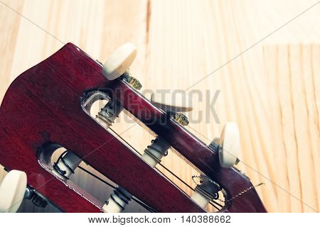 Head and pegs of a guitar on a light wooden background. Musical instrument. Copy space in the top right corner.