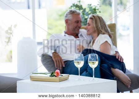 Romantic couple with white wine glasses by rose and gift box on table on foreground