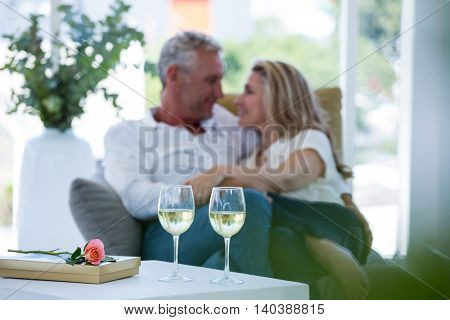 Romantic couple sitting on armchair with white wine and gift box on foreground