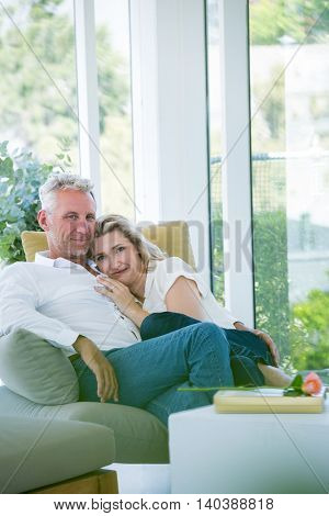 Portrait of romantic mature couple sitting on armchair at home