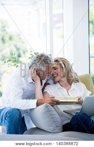 Romantic smiling mature couple with gift box at home