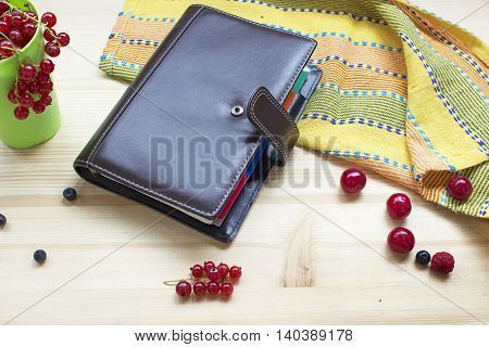 Summer planning - diary on a table with different mix berries wooden background.