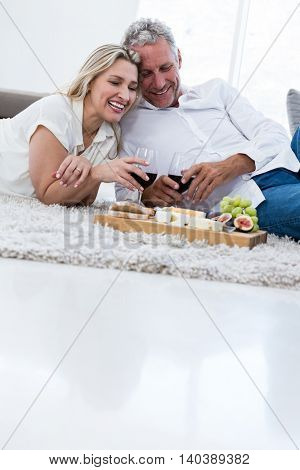 Smiling couple with red wine and food while lying on rug at home