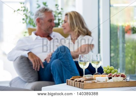 White wine and food on table with romantic couple in background