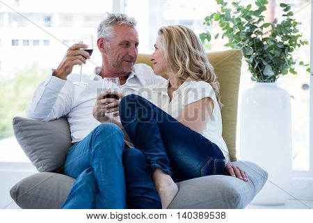 Romantic mature couple having red wine while sitting at home