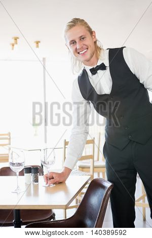 Portrait of waiter standing at table with empty glass in restaurant