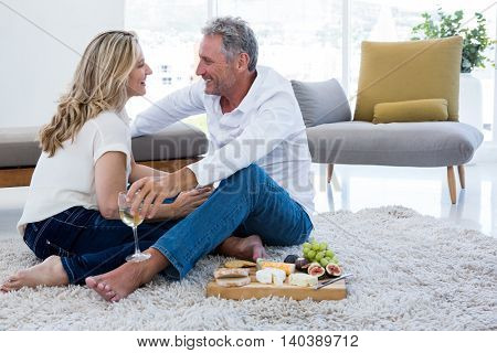 Romantic couple with white wine and food while sitting on rug at home
