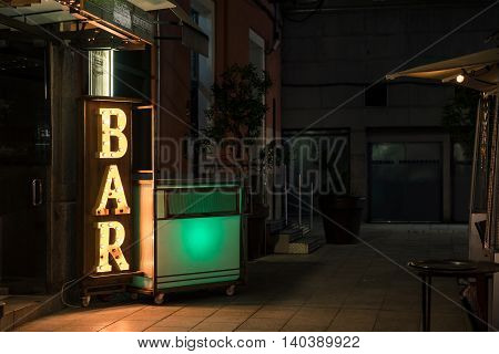 Bar Electric Light Sign On The Buildings Exterior On Dark Night Time In The city