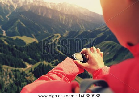 young woman hiker checking the altimeter on sports watch at mountain peak