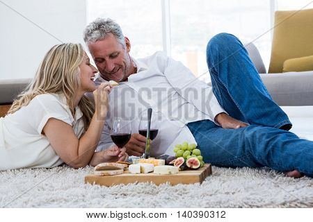 Smiling woman feeding food to man while lying on rug at home