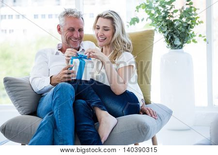 Smiling mature couple with gift box at home