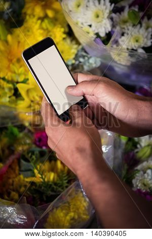 Male florist taking photo of flower bouquet on mobile phone at his flower shop