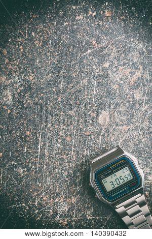 Digital watch on crackle background. Vintage filter.