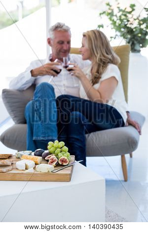 Couple toasting red wine with food on foreground