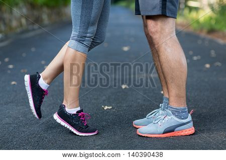 Close-up of couple feet standing on the road