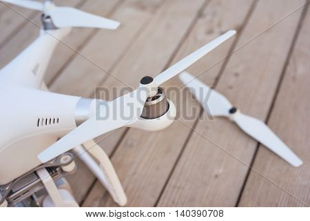 Top view of quadrocopter landed on wooden surface. Selective focus at the propeller.