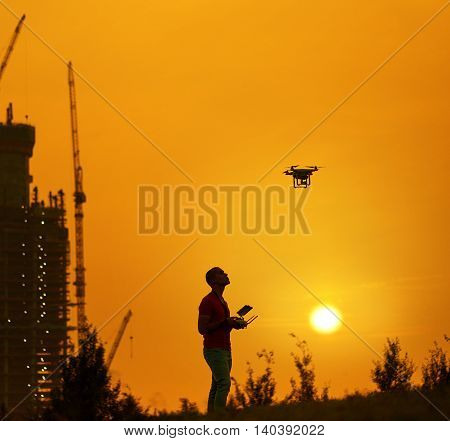 Man controls a quadrocopter at the warm sunset. New building on background.