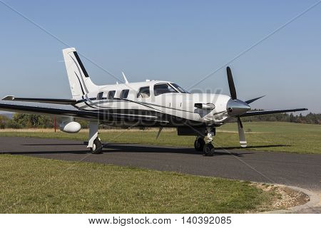 Single small turboprop aircraft on airport runway