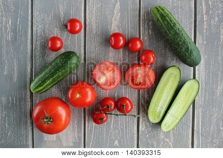 Composition of vegetables on grey wooden desk. Tomato, cucumber. Top view.
