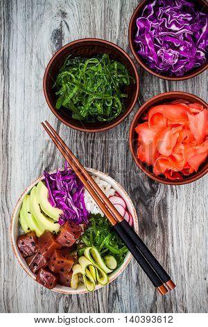 Hawaiian tuna poke bowl with seaweed avocado red cabbage radishes and black sesame seeds