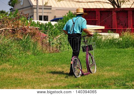 Lancaster County Pennsylvania - June 8 2015: Amish man walking his two-wheeled scooter bicycle which has neither a seat nor pedals *