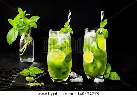 Matcha iced green tea with lime and fresh mint on black stone slate background. Super food drink