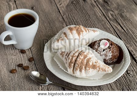 Dessert plate with cakes, a cup of coffee and spoon on a wooden table.