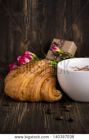 Fresh croissant, cappuccino over wooden table. Toned image. Selective focus