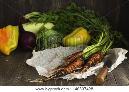 Organic veggies: carrot, cabbage, onion and red peper over vintage wooden table. Selective focus