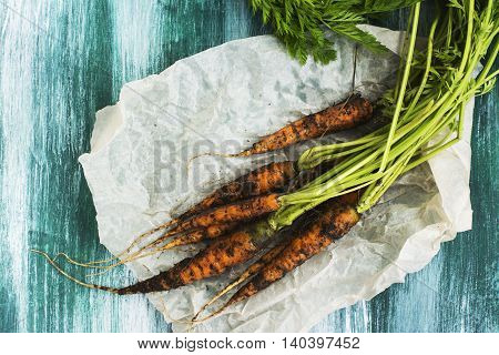 Bunch of fresh organic carrot over grunge wooden table