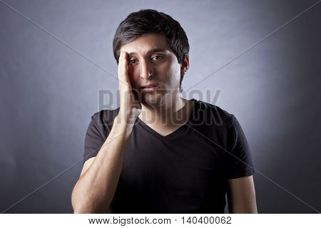 Young man with headache touching forehead on gray background