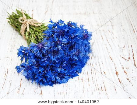 blue cornflowers on a old white wooden background