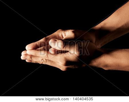 Praying Hands asking for something on the black background