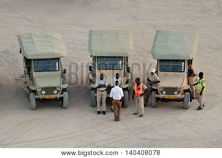 SOSSUSVLEI NAMIBIA - JAN 28 2016: Local guides near the off road vehicles awaiting tourists to excursion in Namib-Naukluft National Park National Park