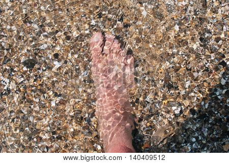Man on beach looking at his feet in the clear water