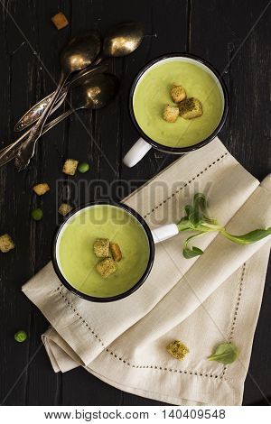 Green spinach and pea cream soup with croutons in enamel mugs over dark wooden table. Natural light. Top view