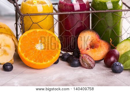 Fresh bright smoothies in small bottles in a wire basket and ingredients over stone kitchen table. Toned image. Selective focus
