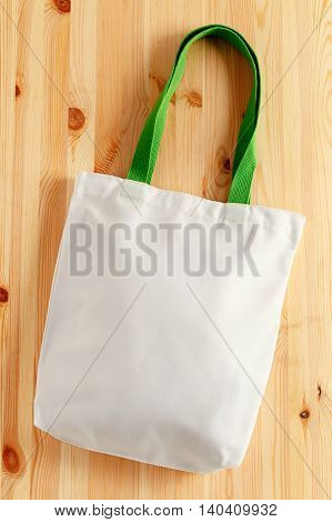 White fabric tote bag on wood background