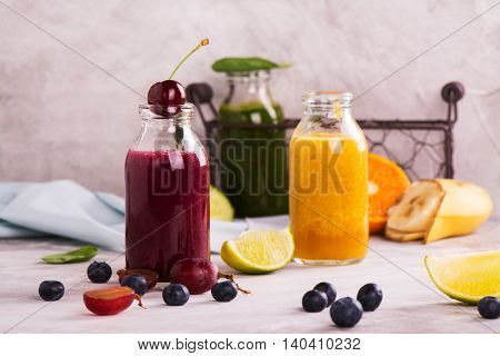 Green, orange, purple smoothies with heap of fruits, vegetables and berries over stone table. Selective focus